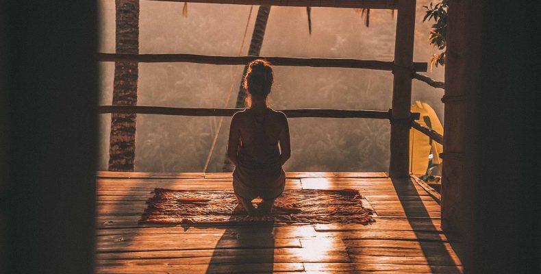 młoda kobieta medytująca o wschodzie słońca