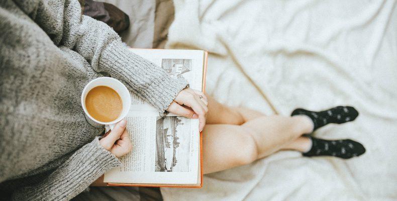 kobieta ubrana w szary sweter i czarne skarpetki z nogami opartymi o łóżko, czyta książkę i pije kawę, widok z góry