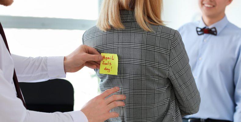 żat na prima aprilis, mężczynza przykleja kobiecie karteczkę na plecy, ężczyżni zartują z koleżanki w biurze
