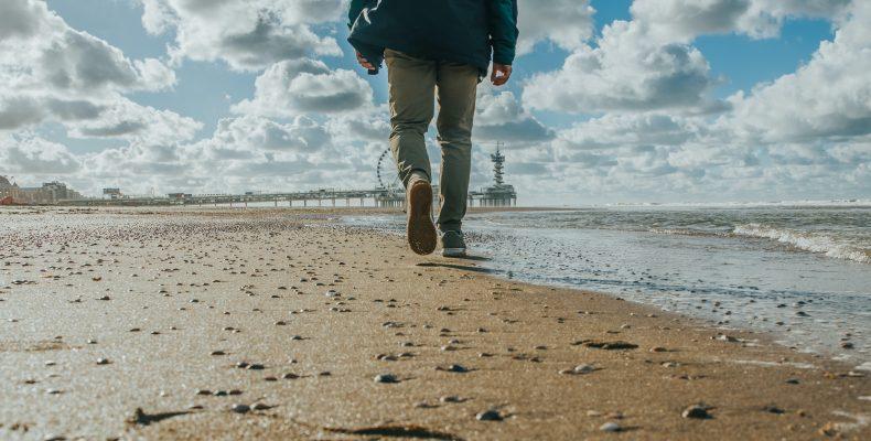 mężczyzna widziny od tyłu idzie plażą pełną muszelek