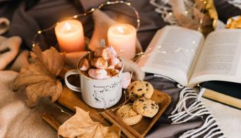 gorąca czekolda z piankami, ciastka oraz książka wśród zapalonych świec i światełek na łóżku